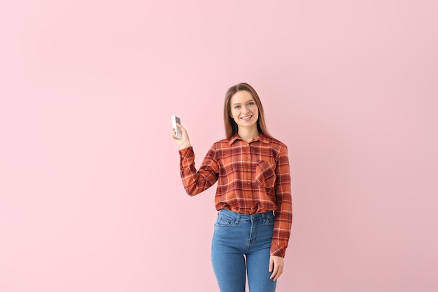 Young woman with air conditioner remote control