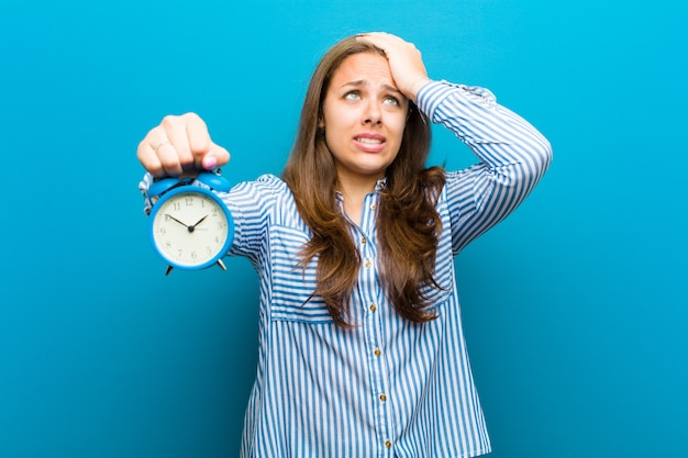 Young woman with alarm clock against blue background