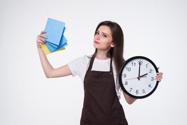 Молодая женщина с будильником и губкой перед чисткой. уборка.