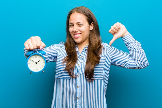 Young woman with alarm clock  blue