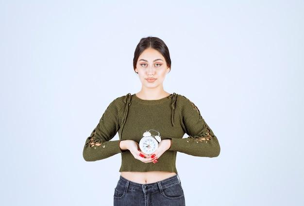 흰색 바탕에 알람 시계 서와 젊은 여자.