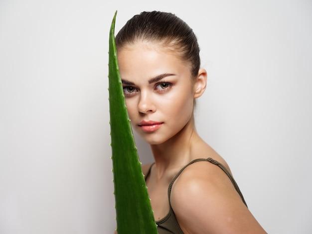明るい背景のきれいな肌のtシャツモデルにアロエの葉を持つ若い女性