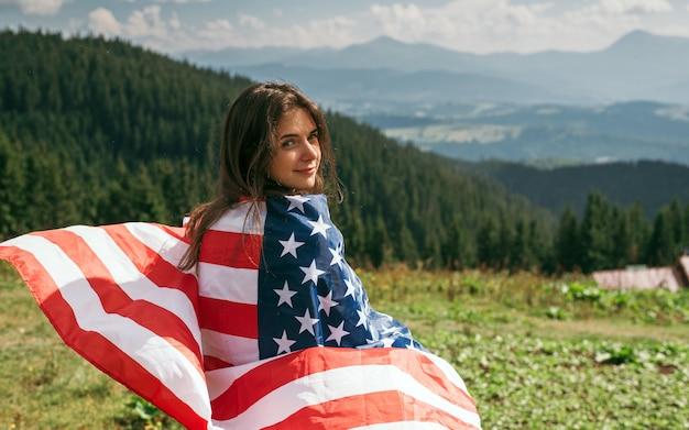 Молодая женщина с американским флагом в руках стоит на вершине горы празднует день независимости сша