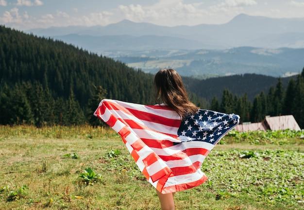 Молодая женщина с американским флагом в руках, стоя на вершине горы