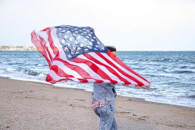 Una giovane donna con una bandiera americana corre in riva al mare. il concetto di patriottismo e celebrazioni del giorno dell'indipendenza.