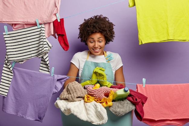 작업 바지에 세탁과 함께 포즈를 취하는 아프리카와 젊은 여자