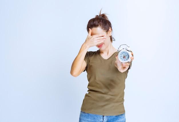 彼女が遅れていることに気づく目覚まし時計を持つ若い女性