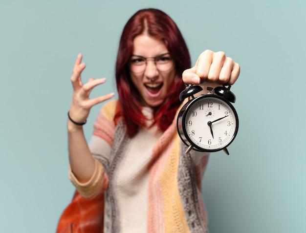 目覚まし時計を持つ若い女性