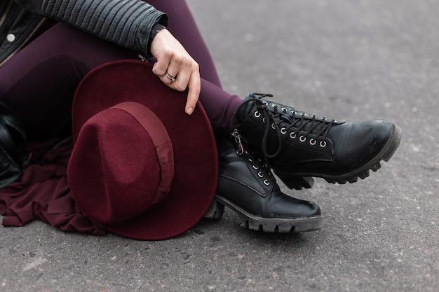가죽 유행 검은 신발 바지에 우아한 빈티지 보라색 모자와 젊은 여자는 아스팔트에 앉아있다.