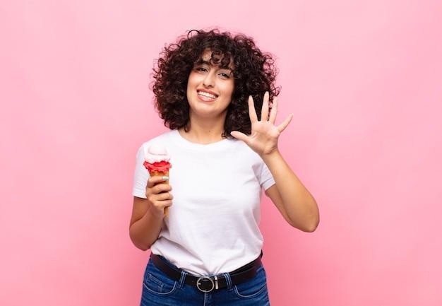 笑顔でフレンドリーに見えるアイスクリームの若い女性、前に手を前に5番または5番を示し、カウントダウン