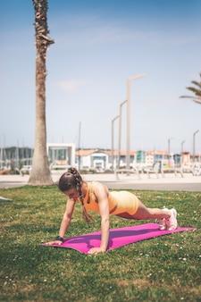 Молодая женщина с оранжевой спортивной одеждой занимается спортом в сквере