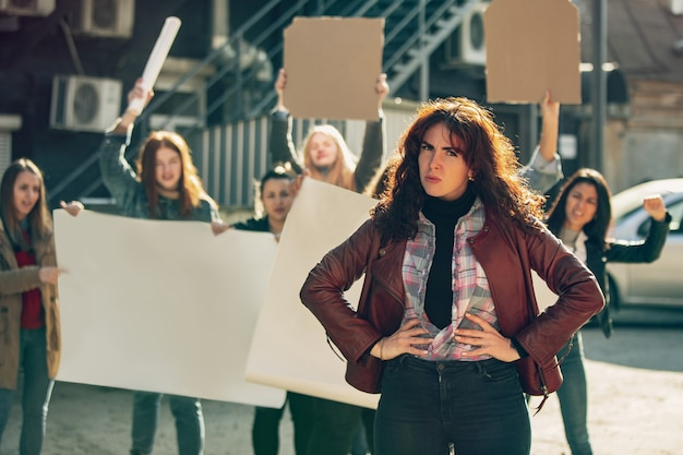 Young woman with angry face in front of people protesting about women's rights and equality on the street. meeting about problem in workplace, male pressure, domestic abuse, harassment. copyspace.