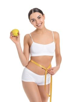 Молодая женщина с яблоком и измерительной лентой на белом.