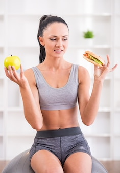 Young woman with apple and hot dog after exercising at home.