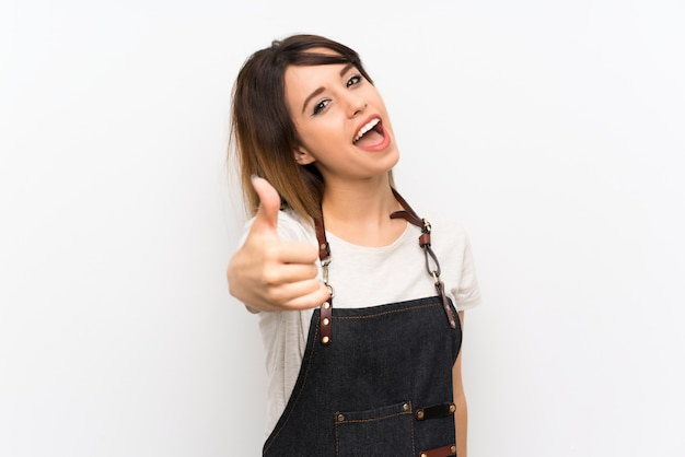 Young woman with an apron with thumbs up because something good has happened