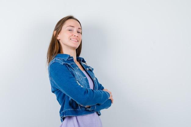 デニムジャケットに腕を組んで誇らしげに見える若い女性。正面図。