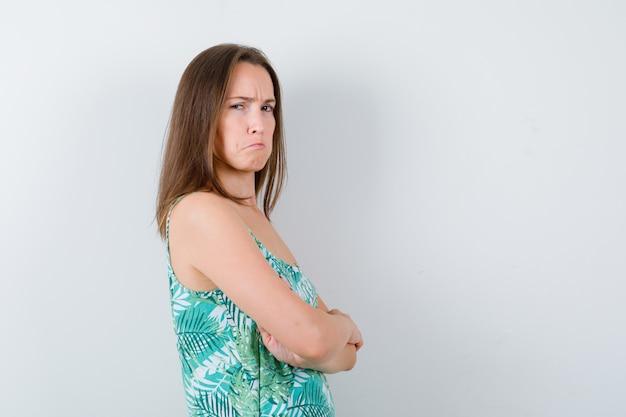 腕を組んで、横に立って、顔をしかめ、下唇を曲げて、不機嫌そうに見える若い女性。