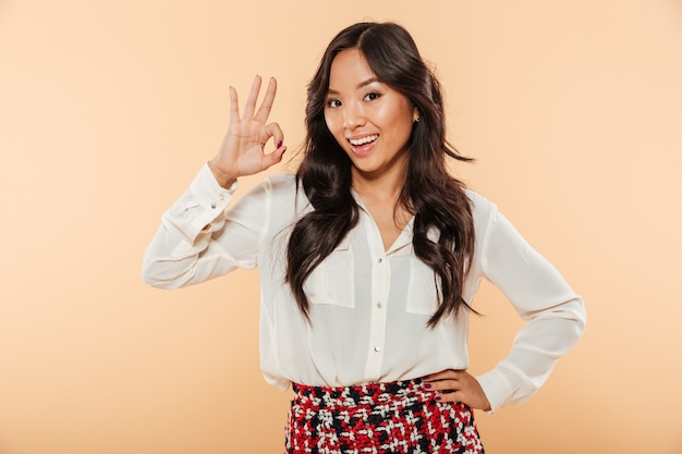 Young woman with asian appearance showing alright gesture being happy and isolated over peach background