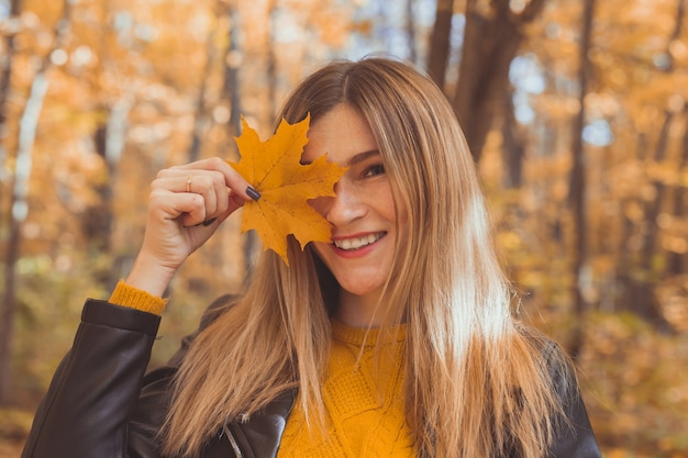 Young woman with autumn orange maple leaf over fall season background