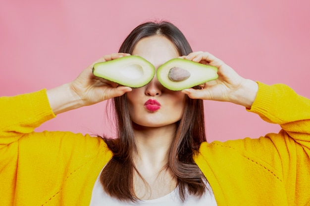 Young woman with avocado halves. beautiful brunette in a yellow sweater. healthy eating and vegetarianism.