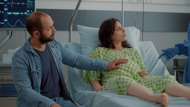 出産を待っている病棟のベッドに座っている赤ちゃんバンプを持つ若い女性。出産と出産についてアフリカ系アメリカ人の看護師からアドバイスを受ける白人カップル