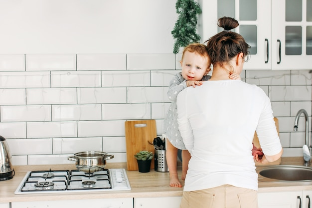Young woman with baby on hands making breakfast at home