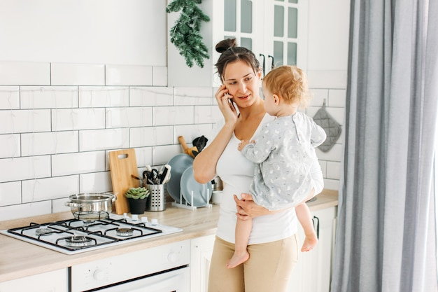 Young woman with baby on hands using mobile at home