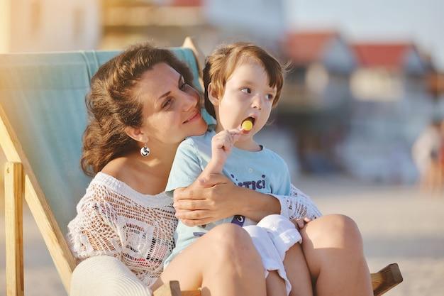 夏のビーチで椅子に座っている赤ちゃんを持つ若い女性