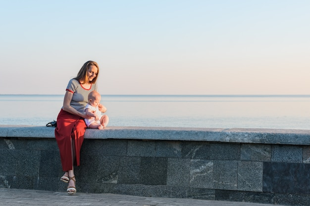 Young woman with baby sitting on sea at sunset. happy motherhood and harmony