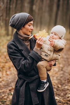 Young woman with baby son walking in autumn park