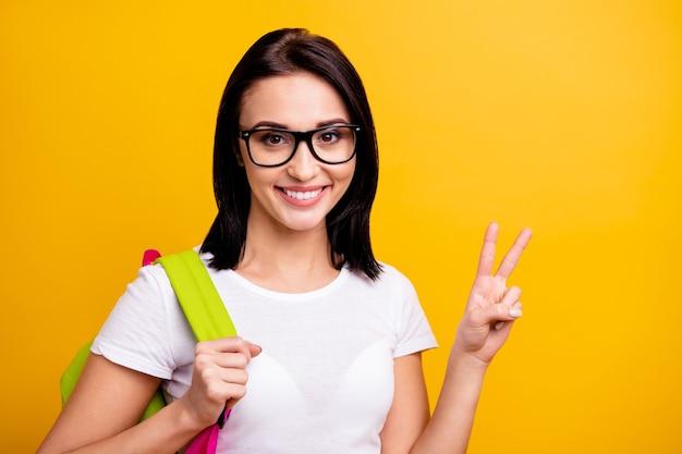 バックパックと本を持つ若い女性