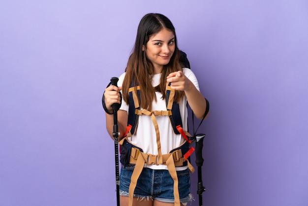 Молодая женщина с рюкзаком и треккинг поляков, изолированных на фиолетовый, указывая фронт с счастливым выражением