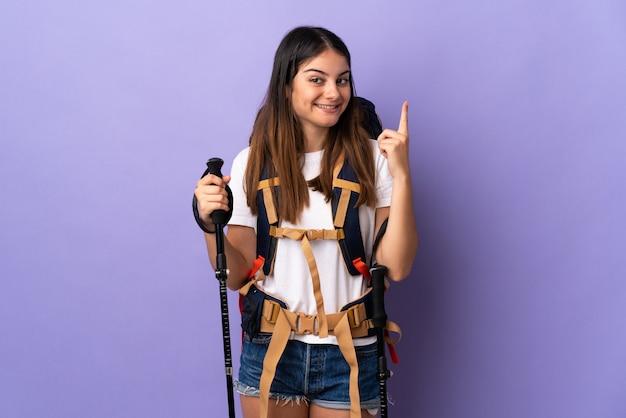 Молодая женщина с рюкзаком и треккинг поляков, изолированных на фиолетовый, указывая отличная идея