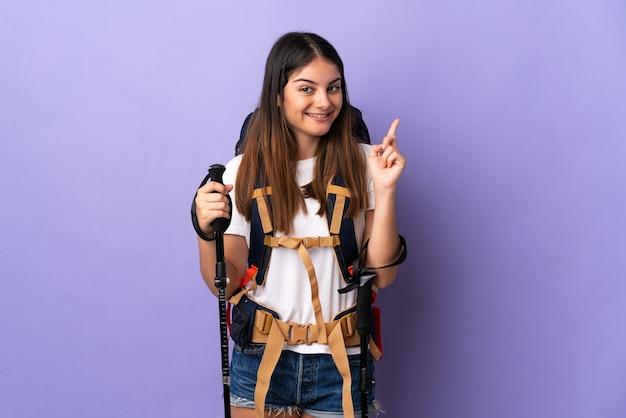 Молодая женщина с рюкзаком и треккинговыми палками, изолированными на фиолетовом, показывает и поднимает палец в знак лучших