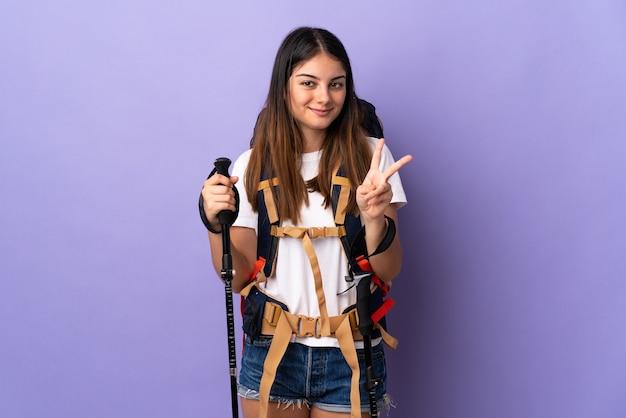 Молодая женщина с рюкзаком и треккинговыми палками изолирована на фиолетовом, улыбаясь и показывая знак победы