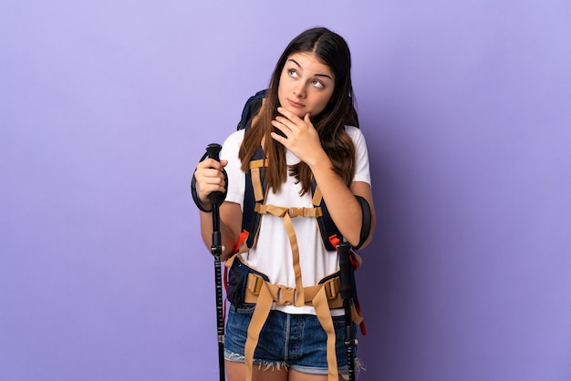 Молодая женщина с рюкзаком и треккинговыми палками изолирована на фиолетовой стене с сомнениями