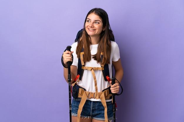 見上げながらアイデアを考えて紫色の壁に分離されたバックパックとトレッキングポールを持つ若い女性