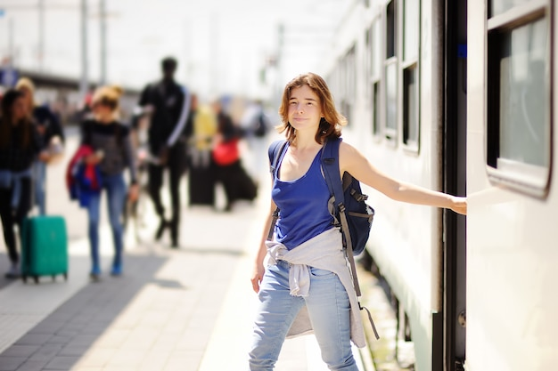 Young woman with backpack getting out of car train.
