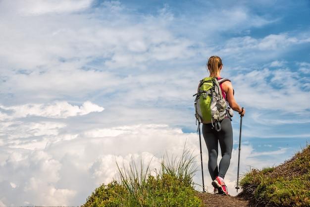 Молодая женщина с рюкзаком, походы в горы
