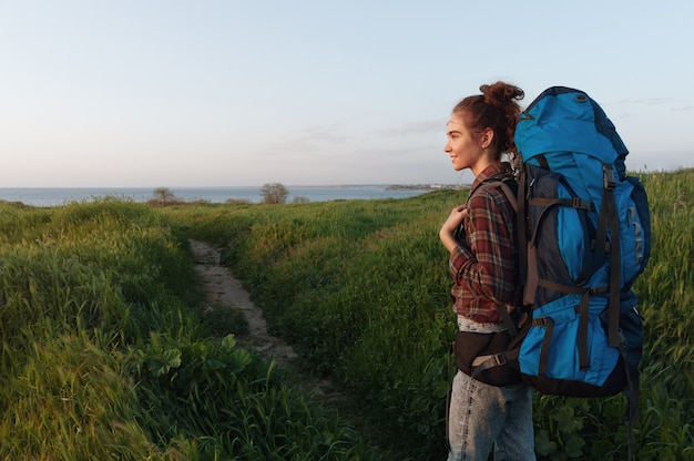 Young woman with backpack hiking in the open air