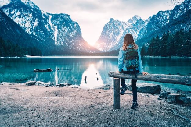 バックパックを持った若い女性は、秋の日没時に山の湖の海岸に座っています。秋にイタリアを旅行します。スリムな女の子、水の反射、雪の岩、緑の木々のある風景。ヴィンテージ調色