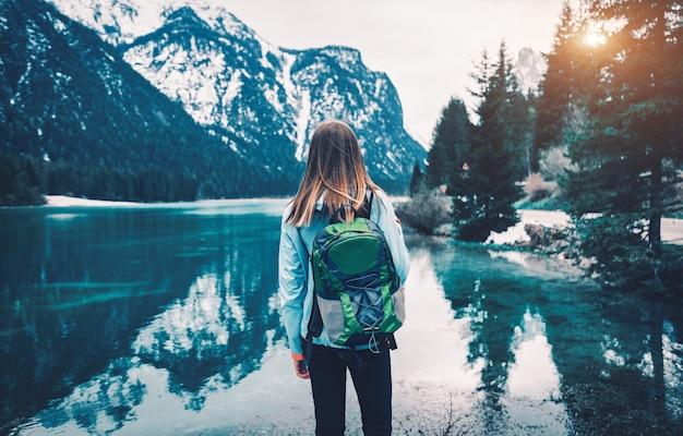 バックパックを持った若い女性が秋の日没時に山の湖の海岸に立っています。秋のイタリア旅行。スリムな女の子、水の反射、雪の岩、緑の木々のある風景。ヴィンテージ調色