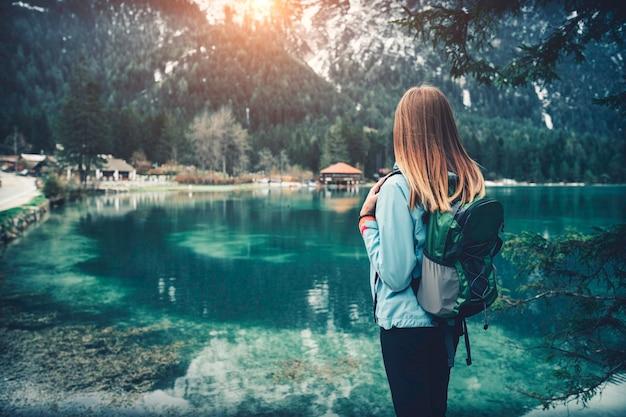 バックパックを持った若い女性は、秋の日没時に山の湖の海岸に立っています。イタリア旅行。スリムな女の子、水の反射、雪の岩、秋の緑の木々のある風景。ビンテージ
