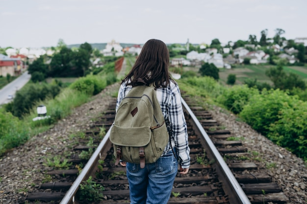Young woman with a backpack on a railway track.