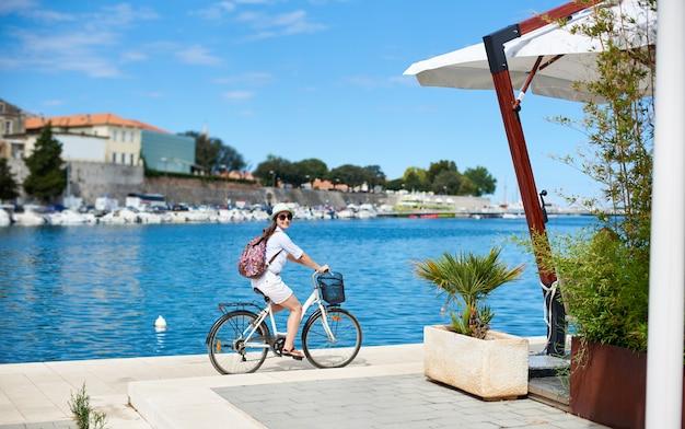 Молодая женщина с рюкзаком езда городской велосипед возле моря