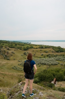 Young woman with backpack standing on cliff's edge and looking to the sky and beautiful nature.