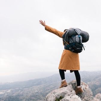 Young woman with backpack standing on mountain rock waving her hand