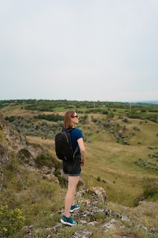 Молодая женщина при рюкзак стоя на крае скалы и смотря к небу и красивой природе.