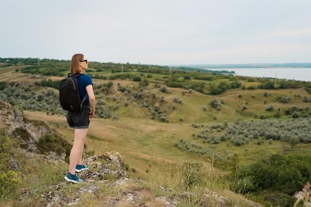 崖の端に立っていると空と美しい自然を見ているバックパックを持つ若い女性。