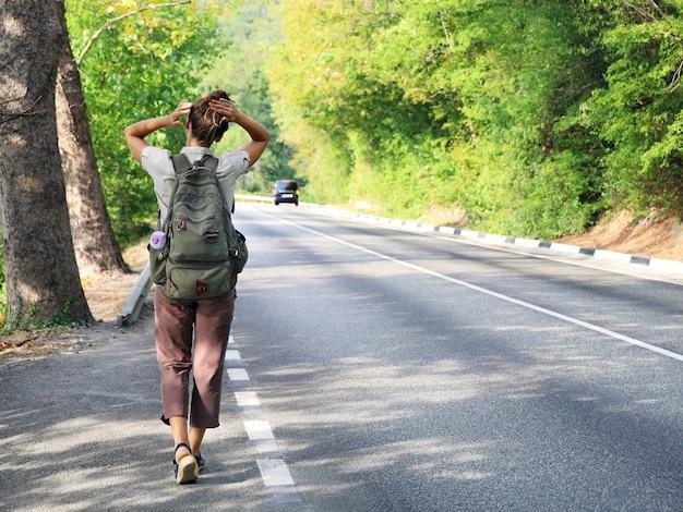 배낭을 든 젊은 여성은 도로 가장자리에 등을 대고 머리카락을 곧게 만듭니다.